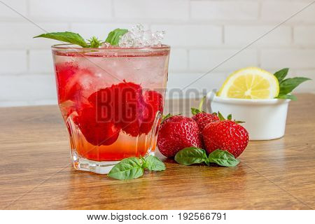 A Refreshing Summer Drink With Ice, Strawberries And Lemon On A Wooden Background. The Concept Of Fr