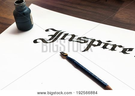 Writer's tools. Ink, paper, pen top view. Inspire calligraphy lettering background. Word drawn with inks on sheet of paper. Drawing lessons, art school, creativity concept