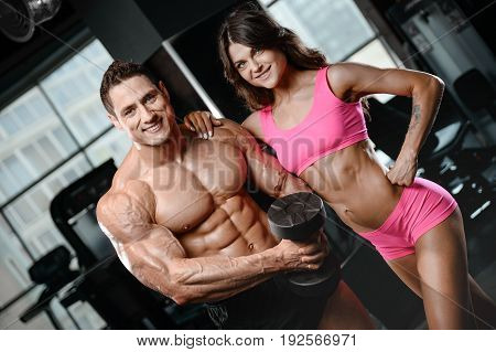 beautiful young sporty sexy couple showing muscle and workout at the gym