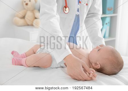 Doctor examining little baby in clinic. Baby health concept