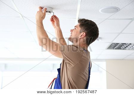 Young electrician installing smoke detector on ceiling