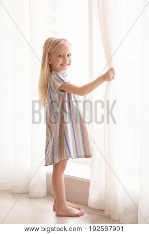 Smiling girl opening curtains