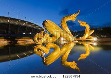 Beautiful gold Serpents king of naga statue in Thai temple with water reflection during blue twilight time night landscape