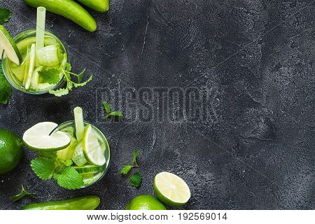 Refreshing drinks with cucumber lime mint on dark background. Detox concept. Copy space top view