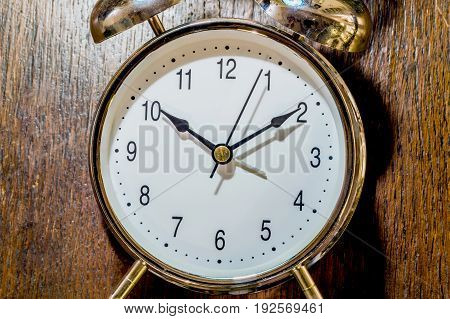Classical alarm clock ringing on wooden background