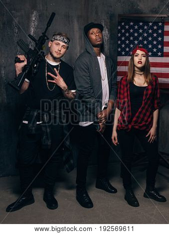 US criminal. Gangsters with weapon. Mixed nationality gang on american flag background. Outlaw, ghetto, social problem, robbery concept