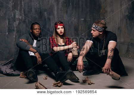 Group of alcoholic young people after party. Youth addiction problem. Tired drunk caucasian girl holding alcohol bottle, sad and depressed guys with tattoo sits near . Students party