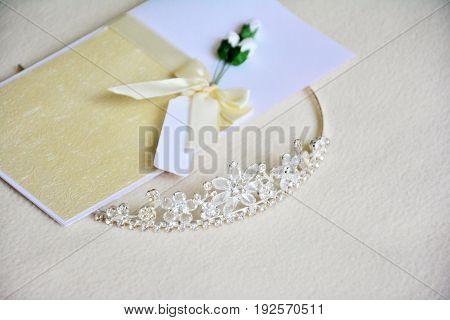 Wedding invitation and bridal tiara on light background