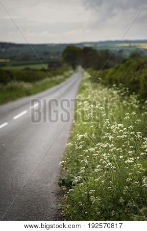 Landscape Image Of Empty Road In English Countryside With Dramatic Stormy Sky Overhead