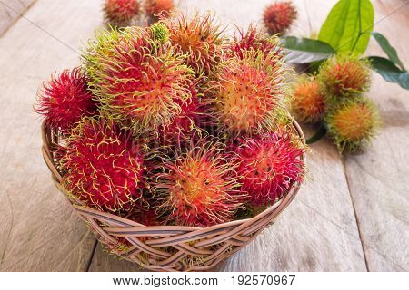 Fresh red rambutan sweet delicious fruit in basket on wood table. Tropical fruit tree native to South - East Asia cultivated in many countries in the region.