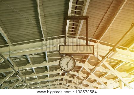 the old analog clock on the roof of railway station in vintage tone color for background