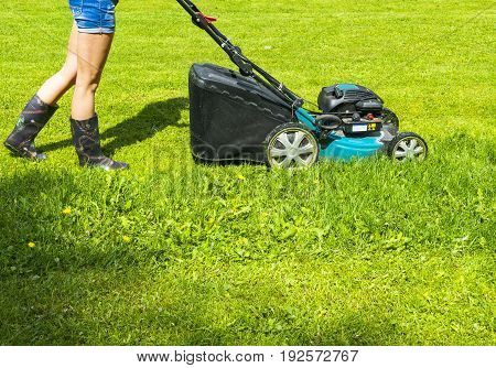 Beautiful girl cuts the lawn Mowing lawns Lawn mower on green grass mower grass equipment mowing gardener care work tool close up view sunny day