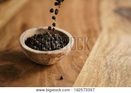 black dry pepper fall into wooden bowl on table, with copy space