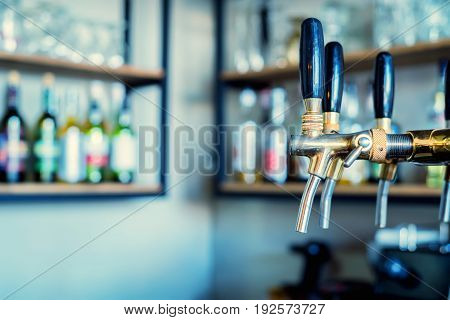Close up of three beer taps in modern bar