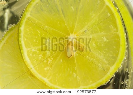Close up concept on piece of lemon or lime in lemonade for wallpaper or background. Half-circle of lemon or lime in sparkling water(soda)in natural tone. Water bubble and half-circle lemon or lime. Lemon or lime sliced abstract background.