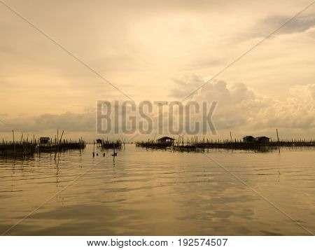 Vintage tone of homestay and floating basket in lake at Kohyo Songkhla Thailand with beautiful sky and clouds. This is traditional fisheries area.
