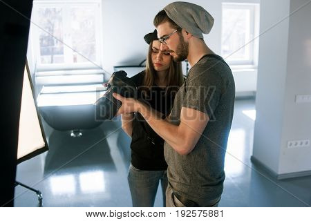Misunderstanding with photographer on photo shoot. Model didn't like photos on camera. Man with camera show pictures to angry woman in during the studio session.