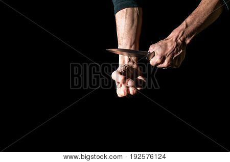 Suicide. Man want to commit suicide by cutting his veins with knife. Low key image, isolated on black background.