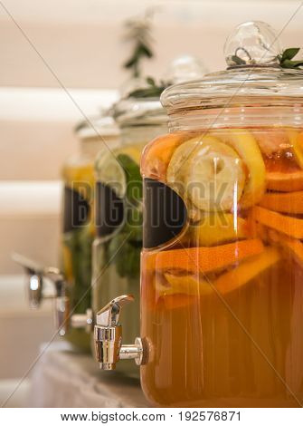 A refreshing drink with orange in large glass jars with tap