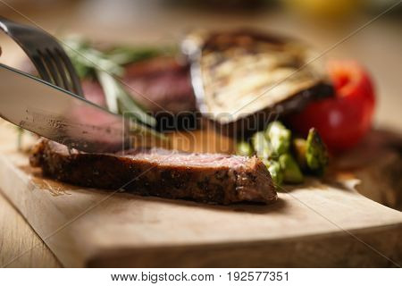 slicing medium rib eye steak with grilled vegetables, shallow focus