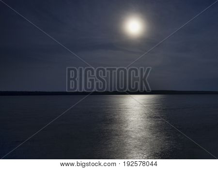 Full moon rising behind a haze over Dore Lake in Saskatchewan