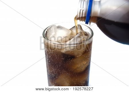 Soft drink from bottle to a glass with ices