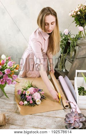 Woman have pack wedding bouquet in wrapping paper. Young beautiful florist make floristry assemble with pink peony and wildflowers in workshop on wooden background