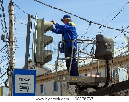 Voronezh, Russia - April 27, 2017: The employee of city services serves a traffic light on Lenin's area of the city of Voronezh