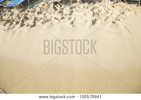 The sand beach with deckchairs close up