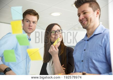 Young businesswoman smiling while standing by male colleagues looking at adhesive notes stuck on glass wall in office