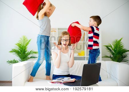 Stressed mother working from home while her children pillow fight