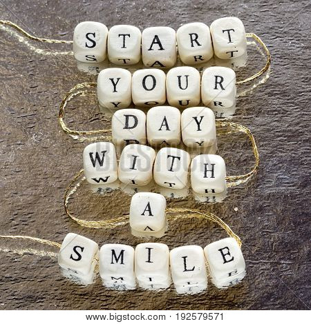 inscription start your day with a smile made from wooden toy blocks stringed on a rope and laying on the shining foil background.