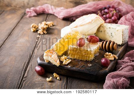 Honeycomb with assorted cheeses, grape and walnuts on old wooden cutting board. Healthy food concept. Copy space.