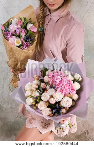 Unrecognizable florist show bouquets of rose and tulip flowers. Young woman with a pink bouquet. Floristic workshop, skill, decor, small business, gift concept