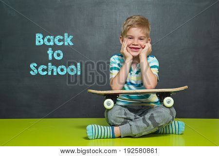 Boy With Skateboard And School Board With Text Back To School