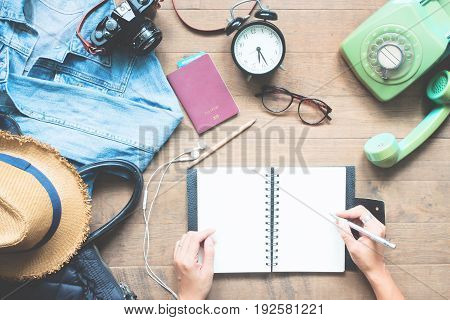 Creative high angle view of travel concept with traveler items and woman hands planning trip on blank notebook