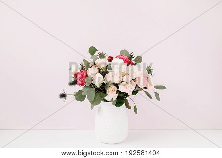 Beautiful flowers bouquet: bombastic roses blue eringium eucalyptus branches in flowerpot at pale pastel pink wall. Floral lifestyle composition.