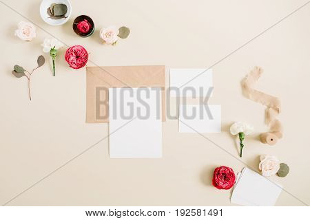 Wedding invitation cards craft envelope pink and red rose flower buds and white carnation on pale pastel beige background. Workspace with paper blank. Flat lay top view