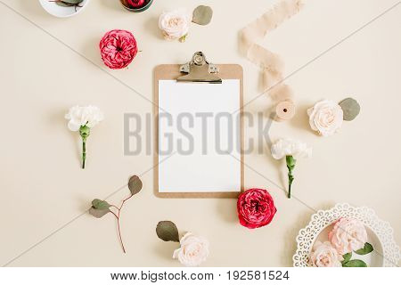 Flat lay floral frame with blank clipboard red and beige rose flower buds white carnation eucalyptus ribbon on pale beige pastel background. Top view decorated concept.