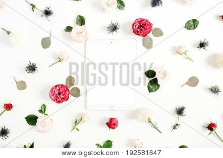 Flat lay floral frame with tablet red and beige rose flower buds on white background. Top view decorated concept.