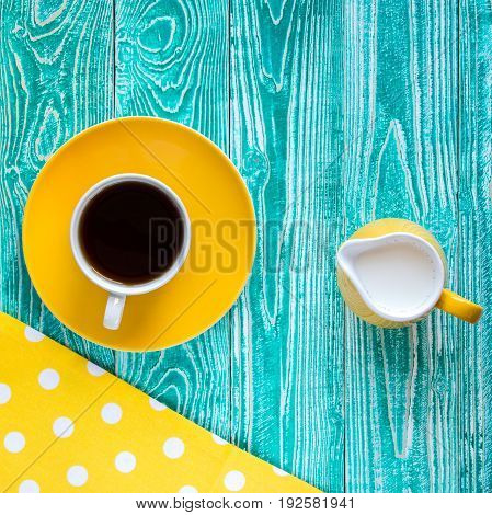 cup of black tea on yellow plate and yellow milk jug on turquoise colored old wooden table with yellow napkin at polka dots top view