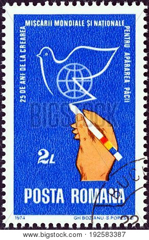 ROMANIA - CIRCA 1974: A stamp printed in Romania issued for the 25th anniversary of World Peace Movement shows hand drawing peace dove, circa 1974.