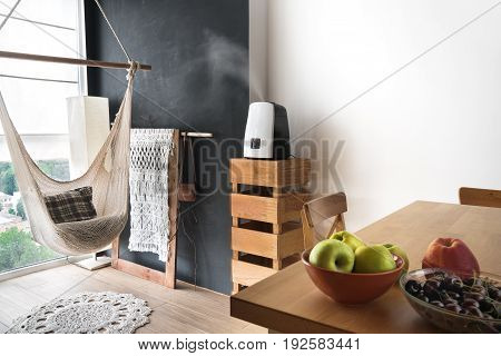 Seductive apartment design in loft and rustic style. Hammock dining table air humidifier and view from the balcony. Cozy housing.