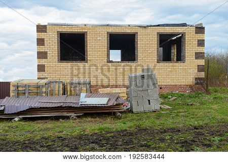 Unfinished brick house with a fence in cloudy weather