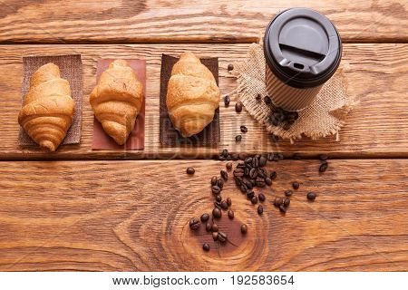 Roasted coffee beans, plastic cup and desserts on wooden background. Closeup of seeds on dark brown cafe table. Top view.