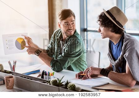 Good start. Portrait of excited young businessman is pointing finger at graphic on paper. He is looking at his coworker and smiling