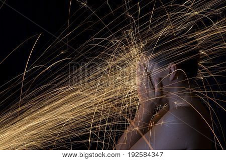 Long exposure photo of a woman blocking glowing sparks artistic conversion