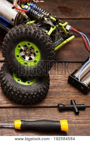 Dismantled broken Rc radio control car crawler model toy repair. Green toy suv in repairshop workplace, closeup