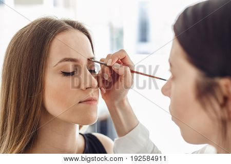 Beautiful young woman gets eyebrow correction procedure. Young woman tweezing her eyebrows in beauty saloon.