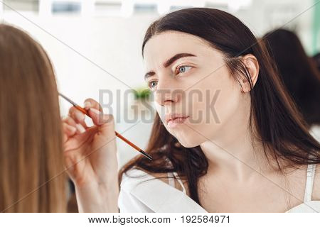 Portrait of a master in a beauty salon during the procedure. The woman doing make-up in the beauty salon to the client.